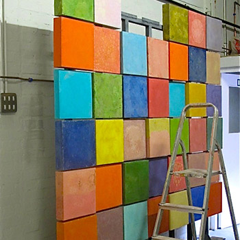 Constructing wall of coloured concrete blocks