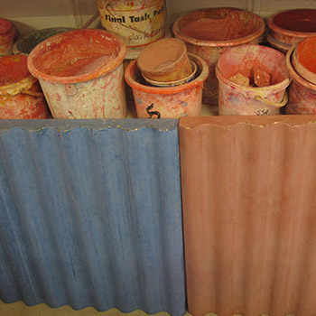 Coloured corrugated concrete blocks with pots of mixed pigment